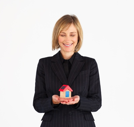 Happy mature businesswoman holding a house photo