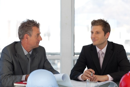 Two colleagues talking together at desk  photo