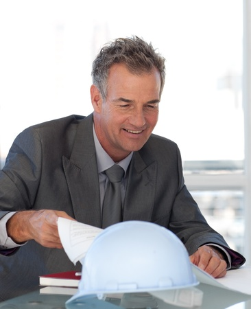 Smiling businessman working at his desk  photo