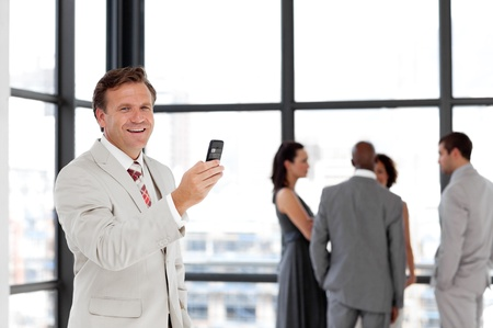 Confident businessman holding a phone at workplace with his colleagues  photo