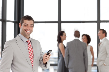 Hispanic businessman holding a phone at workplace with his colleagues  photo