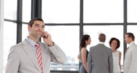Businessman holding a phone at workplace with his colleagues  photo