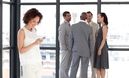 Afro Businesswoman holding a phone at workplace with his colleagues photo