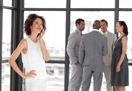 Beautiful Businesswoman holding a phone at workplace with his colleagues photo