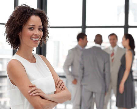 american woman: Bright Businesswoman arms folded with his colleagues