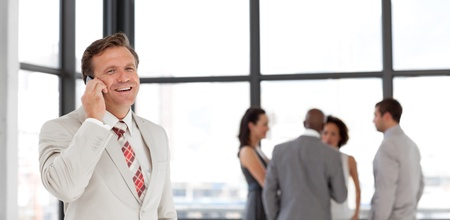 Smiling businessman holding a phone at workplace with his colleagues  photo