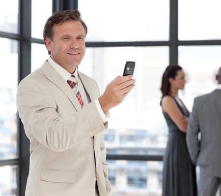 Happy businessman holding a phone at workplace with his colleagues  photo