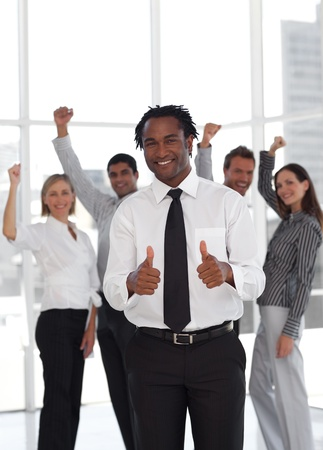 buisinessman: Joyful male manager doing a thumb-up with his team
