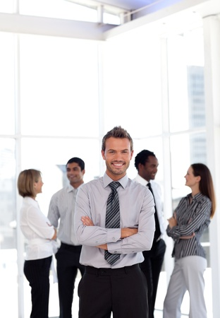 buisinessman: Charming business manager standing at the camera with his team  Stock Photo