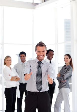 thumbup: positive business manager standing at the camera with his team  Stock Photo