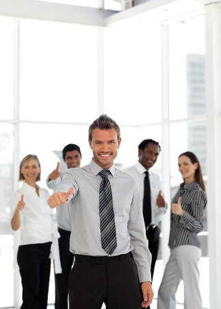 buisinessman: Confident business manager standing at the camera with his team  Stock Photo