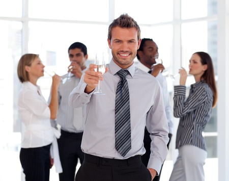 Charming business manager holding a glass with his team Stock Photo - 10233953