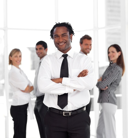 buisinessman: Smiling male manager standing at the camera with his team  Stock Photo
