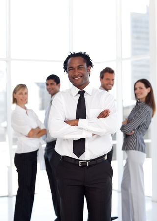 buisinessman: Joyful male manager standing at the camera with his team  Stock Photo