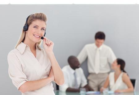 Beautiful female sales respresentative with her team photo