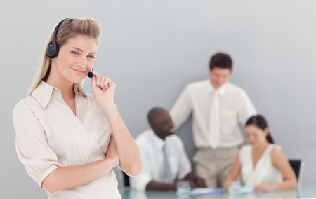 Confident female sales respresentative with her team photo