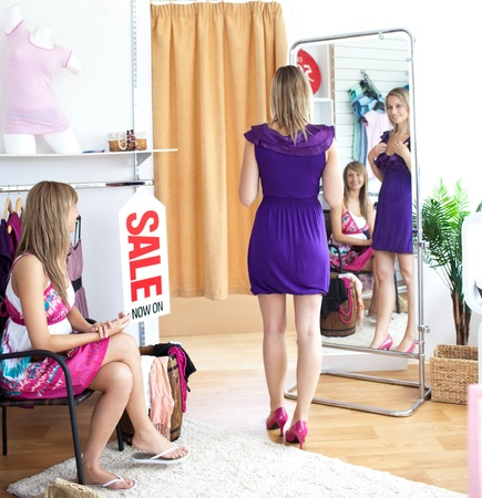 Cute women choosing clothes together photo