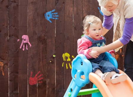 Little girl and her mother having fun with a chute at the playground Stock Photo - 10248035