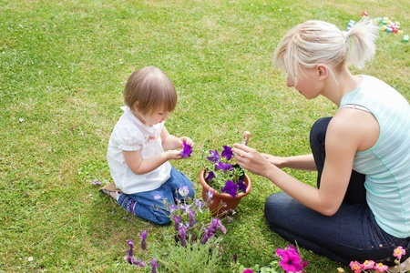 Blond Mother showing her daughter a purple flower  photo