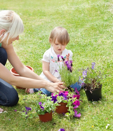 Smiling Mother showing her daughter a purple flower  photo
