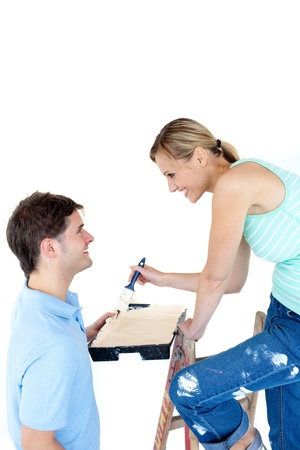 Happy couple painting a room in their new house Stock Photo - 10250354