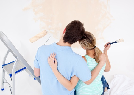 paintrush: Young couple looking at a painted wall  Stock Photo