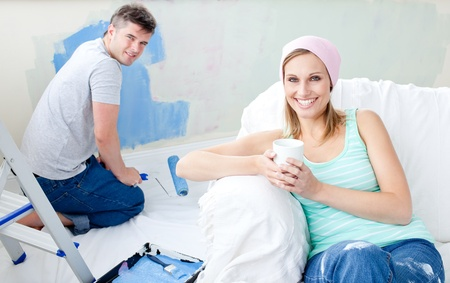 paintrush: Bright woman relaxing boyfriend paint the room Stock Photo
