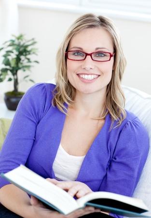 intellect: Ritratto di una donna attraente con occhiali da lettura di un libro seduto su un divano Archivio Fotografico