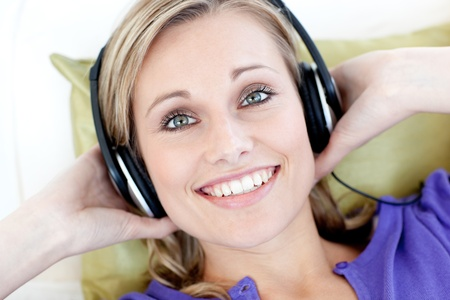 Portrait of smiling woman  listening music looking at the camera photo