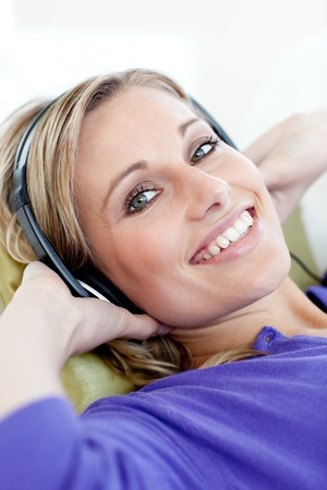 Charming woman lying down on sofa listening music at home photo