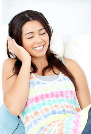 Radiant young woman sitting on sofa and listening music Stock Photo - 10250139