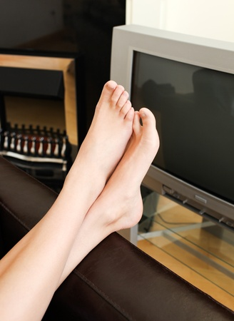 unwound: Unwound woman lies on sofa and watches TV