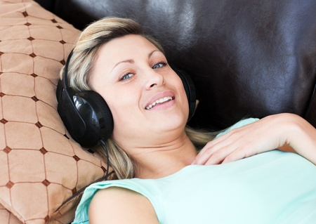 Smiling woman lies on a sofa and listen music photo