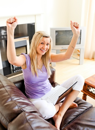 Cheering woman sitting on sofa and working  Stock Photo - 10250073