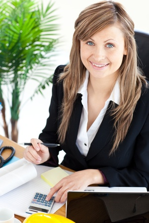 Smilling businesswoman working in her office with a calculator photo