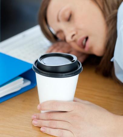 Languorous woman sleeping on table in office  photo