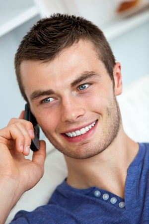 Handsome young man talking on phone in living room photo