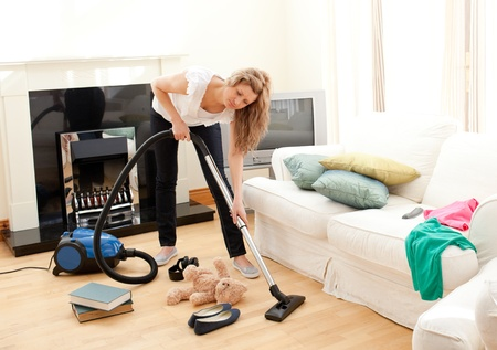 Portrait of a bored woman vacuuming  photo
