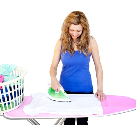 Glowing woman ironing her clothes on a ironing board against white background Stock Photo - 10247002