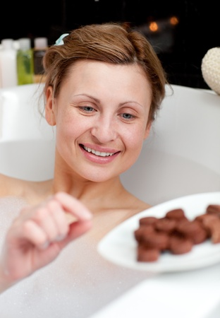 Bright woman eating chocolate while having a bath photo
