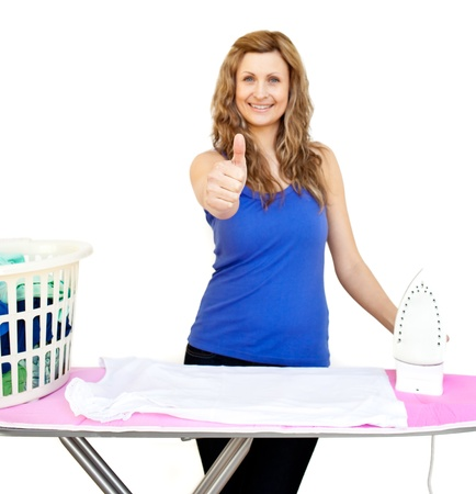 Handsome woman standing behind an ironing board with thumbs up against white background Stock Photo - 10245852
