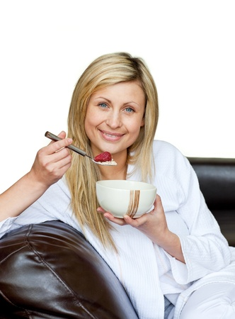 Charming woman eating cereals on the sofa against white background photo