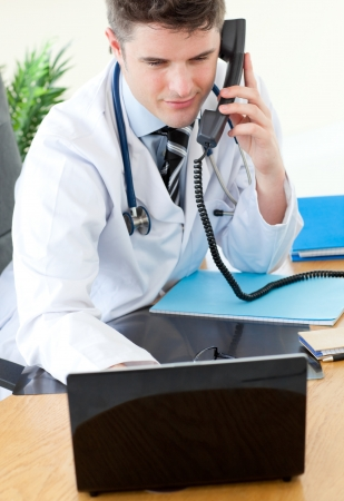 Positive male doctor on phone using his laptop photo