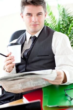 Serious businessman drinking a coffee while reading a newspaper  photo