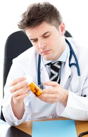 Serious male doctor holding pills sitting at his desk in a practice photo