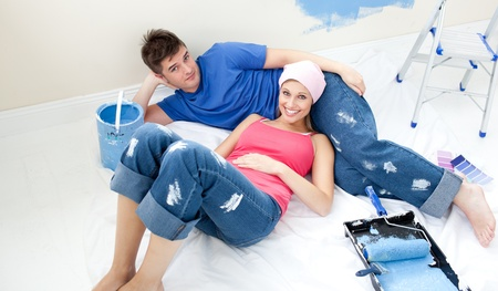 Young couple relaxing after painting a room in their new house photo