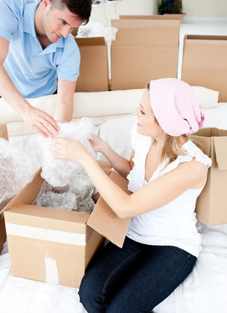 Ambitious young couple unpacking boxes with glasses photo