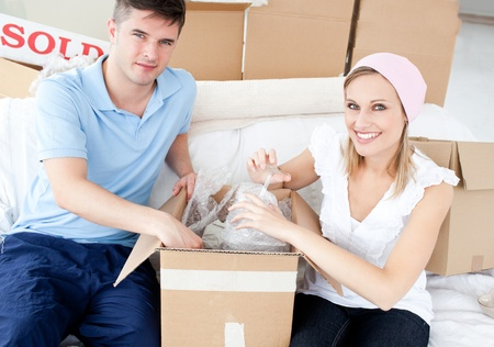Smiling young couple unpacking boxes with glasses in their new house Stock Photo - 10249978