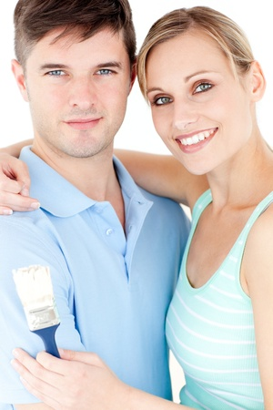 Portrait of a cheerful young couple holding a paint brush against white background photo