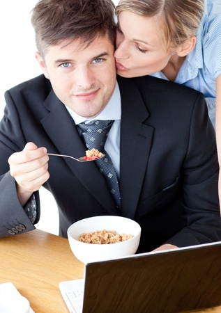 Smiling businessman eating breakfast using laptop while wife kissing his cheek Stock Photo - 10248593